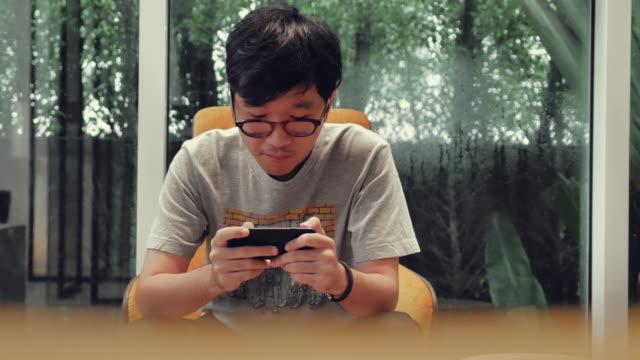 asian man playing games on smartphone - развлекательные игры стоковые видео и кадры b-roll