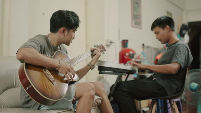 Asian man playing his guitar on the house with friends stock video