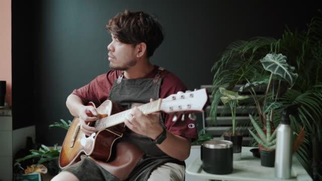 asiatisk man spelar musik tillsammans genom ett videosamtal på internet - gitarrist bildbanksvideor och videomaterial från bakom kulisserna