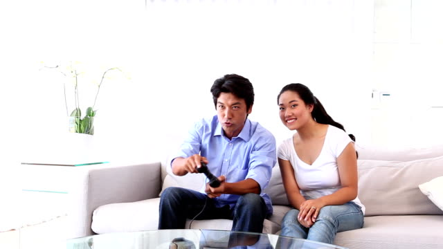 Asian man playing video games with girlfriend