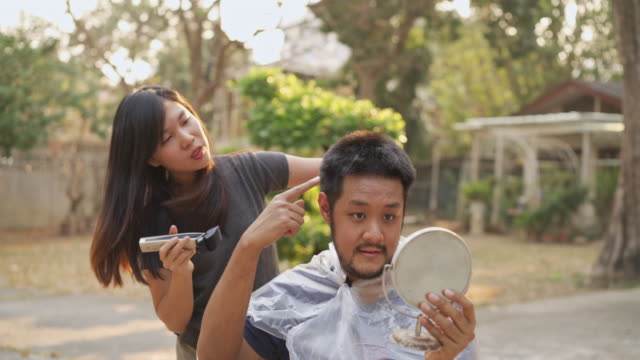 asian man point on his head to asking to shaving his hair cutting hair by clipper at home in covid-19 corona virus situation to help flatten the curve - friseur lockdown stock-videos und b-roll-filmmaterial