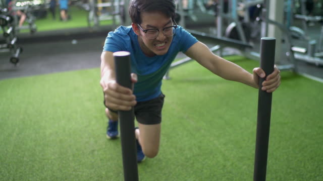 SLO MO Asian man Pushing Prowler Sled in Gym with turf floor