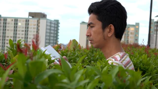 책을 읽고 야외에서 책을 뒤집는 아시아 남자 - 중년 남자 스톡 비디오 및 b-롤 화면