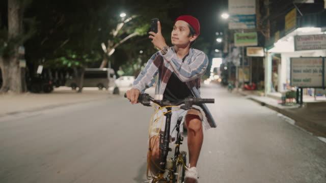 Asian man riding his bicycle and take photo at night