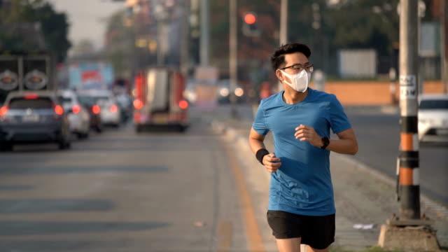 stockvideo's en b-roll-footage met slo mo aziatische man draait in de stad verkeer kruispunt met luchtvervuiling masker in chiang mai, thailand - luchtvervuiling