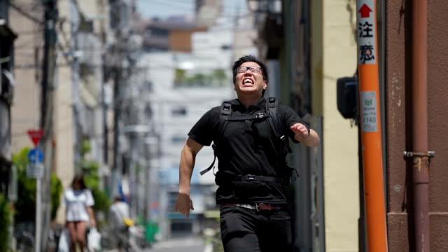 仕事に遅れて通りを走るアジア人の男。 - 東アジア点の映像素材/bロール