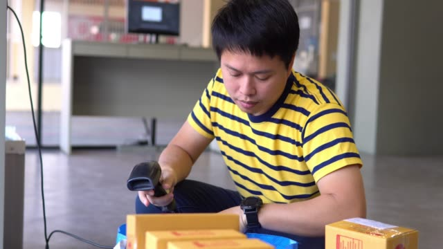 asian man scanning packages with a handheld barcode scanner. - banchi scuola video stock e b–roll