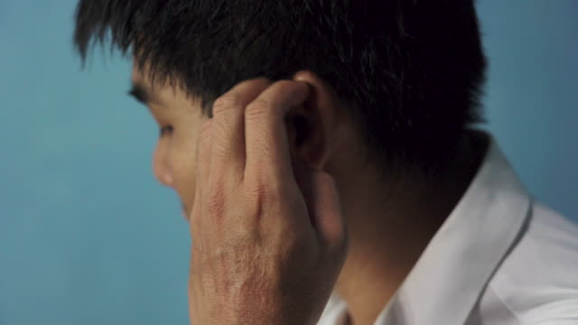 Asian man scratching their ears because of the itch Asian man scratching their ears because of the itch ear stock videos & royalty-free footage