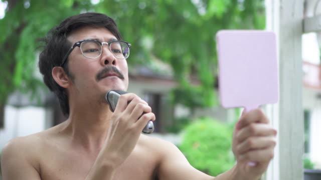 Asian man shaving his beard in rainy day