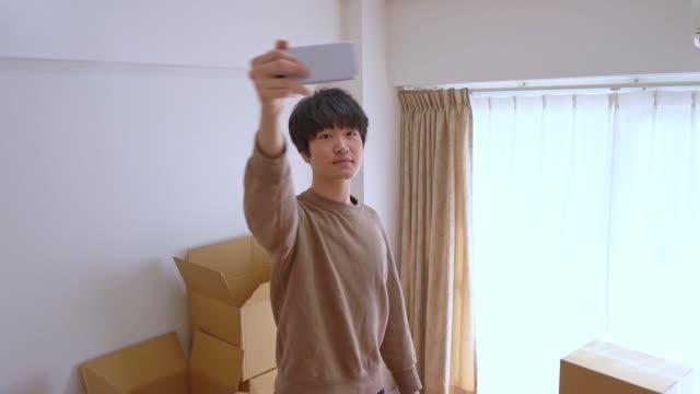 "vídeos de stock e filmes b-roll de asian man shooting video and saying ""i moved!"" - 20 24 anos"