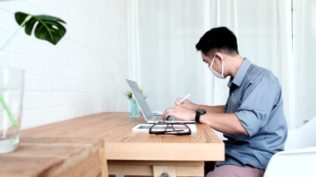 asian man sitting at desk with sneeze guard on it and using computer laptop in home office,  wearing protective face mask   for protection against coronavirus during covid-19 pandemic - new normal video stock e b–roll