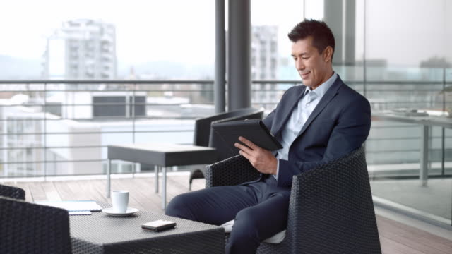 Asian man sitting in the terrace lounge of a business building in and working on the digital tablet Wide handheld shot of an Asian man sitting in the terrace lounge of a business building in the city and working on his digital tablet. Shot in Slovenia. businesswear stock videos & royalty-free footage