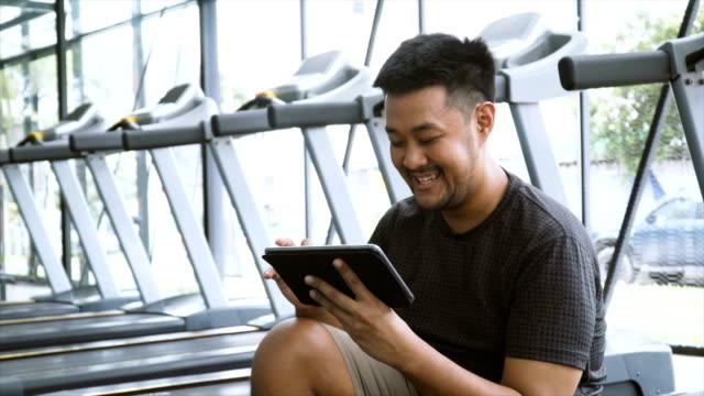 ms asiatiska man sitter på ett löpband som njuter av en digital tablett - gym skratt bildbanksvideor och videomaterial från bakom kulisserna