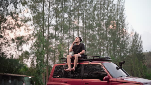 Asian man sitting on the roof of the car and drink coffee