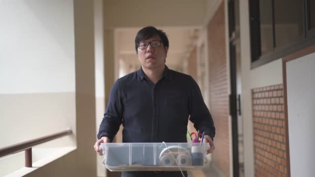 Asian Man Stops to wipe sweat while carrying a box and walking for moving or moving office concept