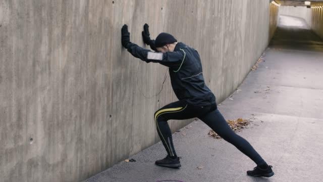 asian man stretching before run (slow motion) - rozgrzewka filmów i materiałów b-roll