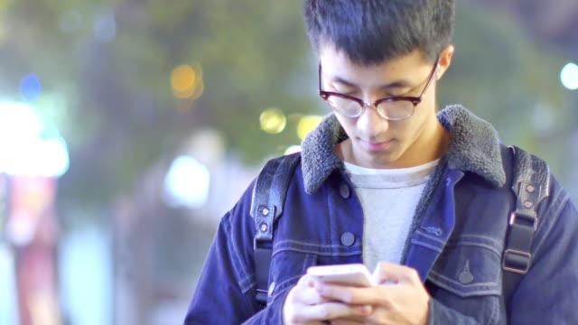 アジア人の学生がキャンパスの夜携帯電話を保持しています。 ビデオ