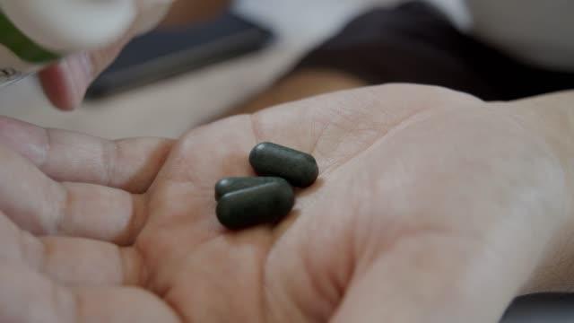 Asian man taking the green medicine on hand.