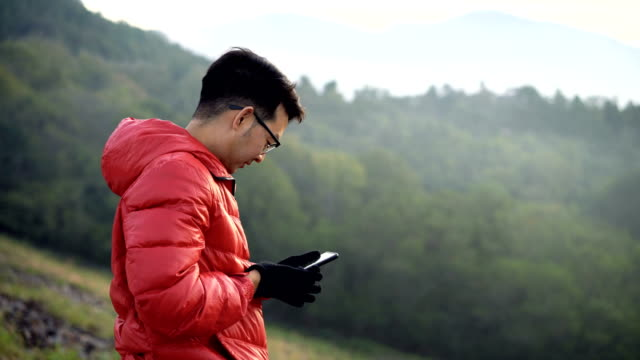Asian Man talking a photo of stunning view from smartphone video