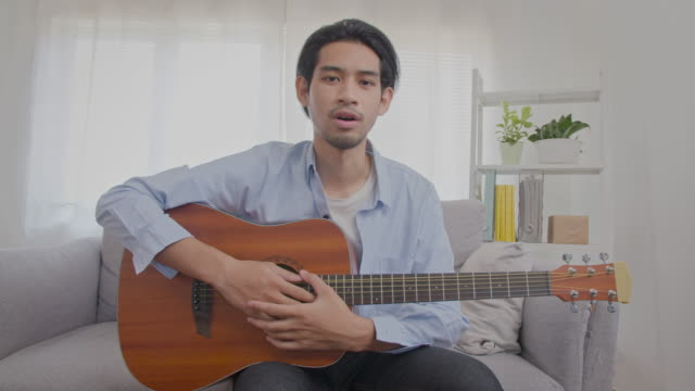 Asian Man teaching guitar online