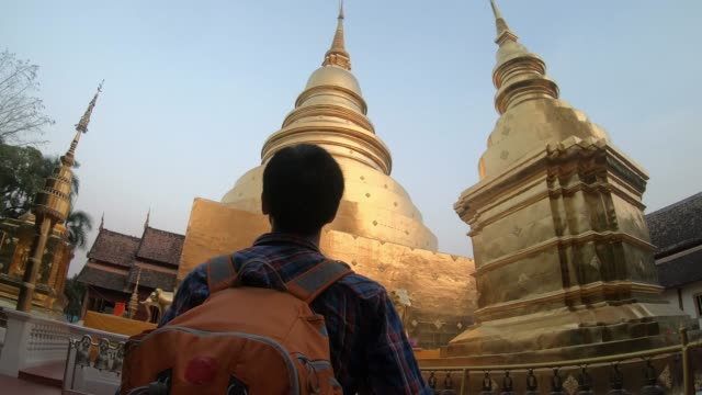 Asian man tourist walks inside the temple with his backpack