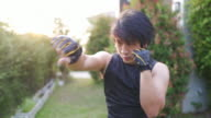 istock Asian man training punch in air at front yard. 1218727019