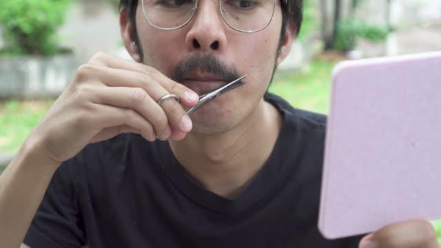 Asian man trimming his moustache