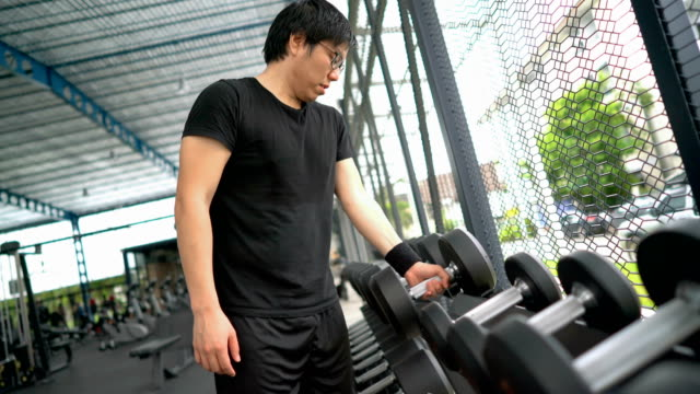 Asian man trying to pick heavy dumbbell in gym video
