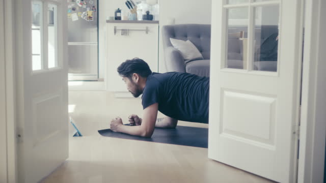 vídeos de stock e filmes b-roll de asian man uses digital tablet to learn plank position - home