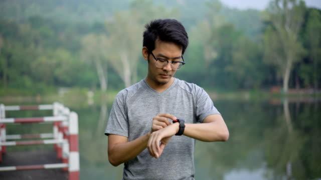 uomo asiatico che usa hr smart watch per praticare la sua corsa - computer indossabile video stock e b–roll