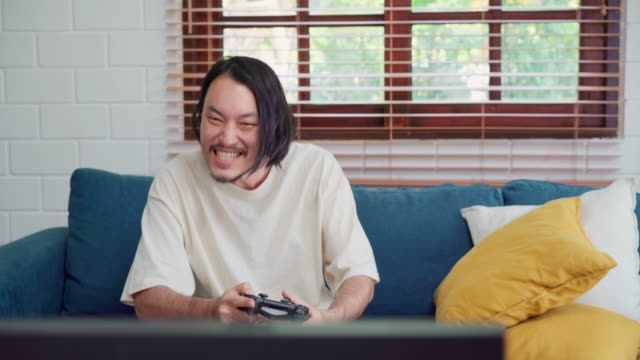 vídeos de stock e filmes b-roll de asian man using joystick playing video games in television in living room, male feeling happy using relax time lying on sofa at home. men play games relax at home concept. - man joystick