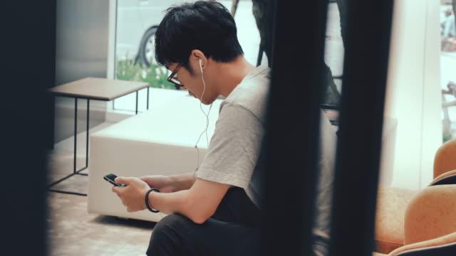 vídeos de stock e filmes b-roll de asian man using mobile phone at sofa. - 25 29 anos