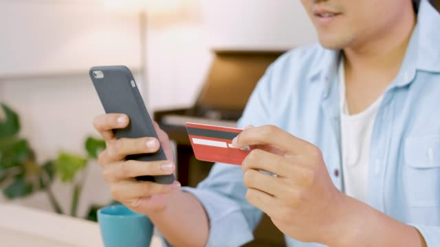 Asian man using mobile phone online shopping with red credit card in kitchen at home.Digital lifestyle concept.