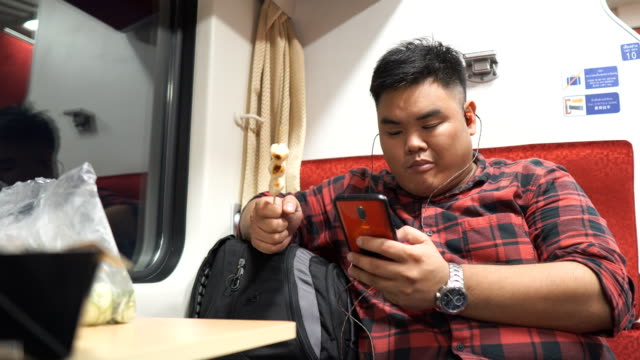 Asian man using mobile smartphone in train video