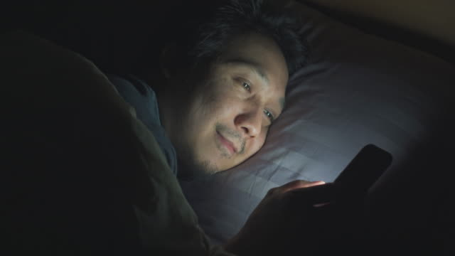 Asian man using smart phone on bed at nighttime