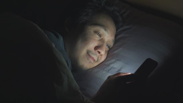 夜間にベッドでスマートフォンを使用するアジア人男性 - スマホ ベッド点の映像素材/bロール