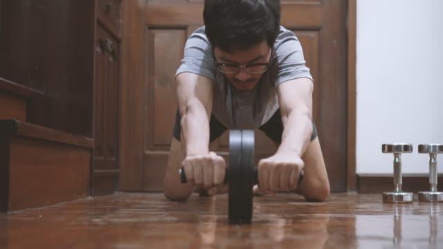 Asian man utilizing ab-wheel at home Asian man utilizing ab-wheel at home bodyweight training stock videos & royalty-free footage