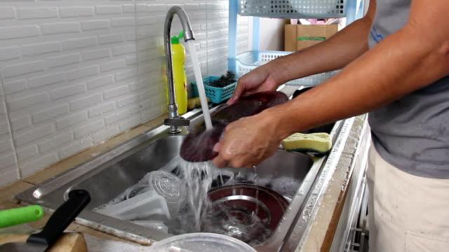 Asian man washing kitchenware Asian man washing kitchenware at house washing dishes stock videos & royalty-free footage