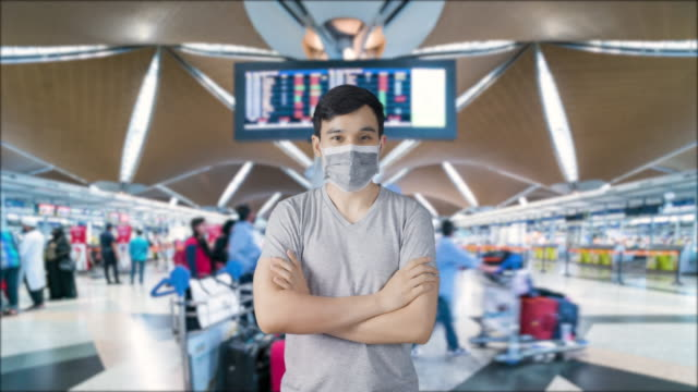 Asian man wearing a mask at Airport terminal (timelapse background) for prevention of Novel Coronavirus nCoV ( COVIC-19) pandemic