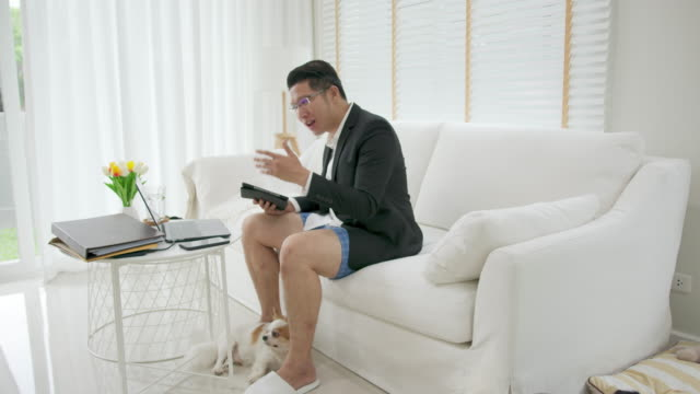 asian man wearing a suit or business wear on top and sweatpants or boxers on bottom. businessman video conference using laptop and tablet online meeting.working from home and working remotely. - pantaloncini video stock e b–roll