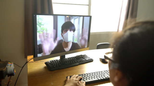 asian man wearing mask video call to his family that stayed at home because quarantined - tajowie filmów i materiałów b-roll