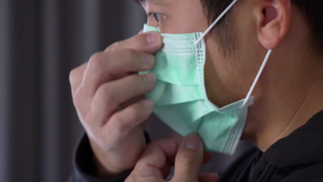 asian man wearing surgical mask to protect corona virus side view - mask стоковые видео и кадры b-roll