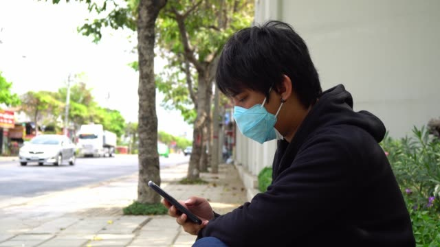 asian man with green hygienic mask prophylactic using smartphone. Health and care concept.
