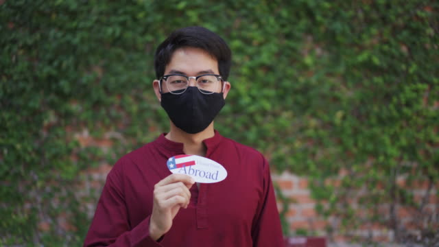 Asian man with protective face mask holding I voted from Abroad sticker after voting in an election during covid-19 coronavirus situation