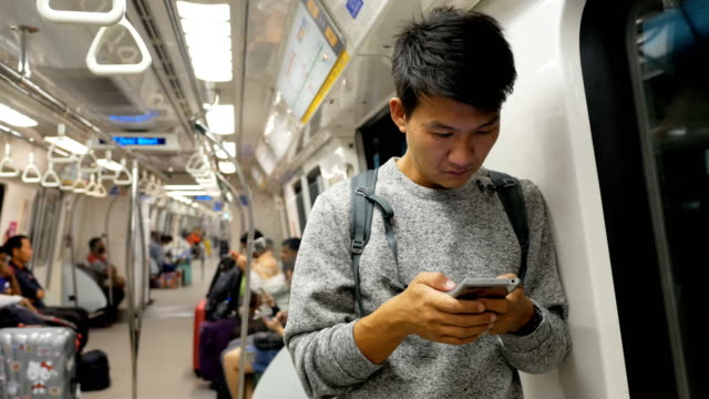 asian man with smartphone in subway