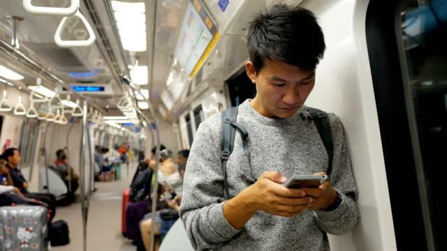 asiatisk man med smartphone i tunnelbanan - kinesiskt ursprung bildbanksvideor och videomaterial från bakom kulisserna