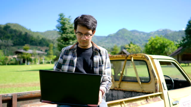 Asian Man working on Laptop Outdoors