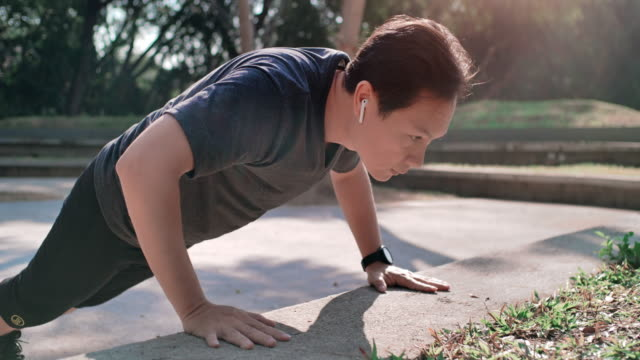 Asian man working out by doing push up exercises and listening to music Asian man working out by doing push up exercises and listening to music. push ups stock videos & royalty-free footage