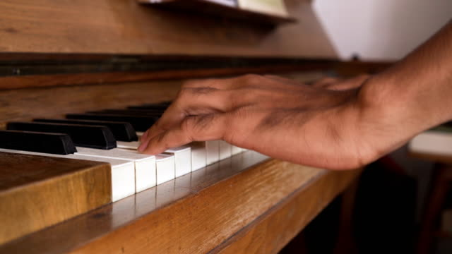 Asian man's hand try to play Piano keyboard while standing
