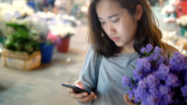 携帯電話を使用してアジア市場: 魅力的な女性 - 花市場点の映像素材/bロール